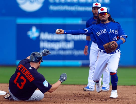 Toronto Blue Jays shortstop Freddy Galvis (16) throws to first for the double play as Detroit Tigers right fielder Dustin Peterson (13) slides into second base in the second inning of a spring training baseball game at Dunedin Stadium on Feb. 23, 2019.