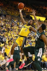 1131879283.jpg ANN ARBOR, MICHIGAN - FEBRUARY 24:  Zavier Simpson #3 of the Michigan Wolverines tries to get a first half shot over Xavier Tillman #23 of the Michigan State Spartans at Crisler Arena on February 24, 2019 in Ann Arbor, Michigan. (Photo by Gregory Shamus/Getty Images)