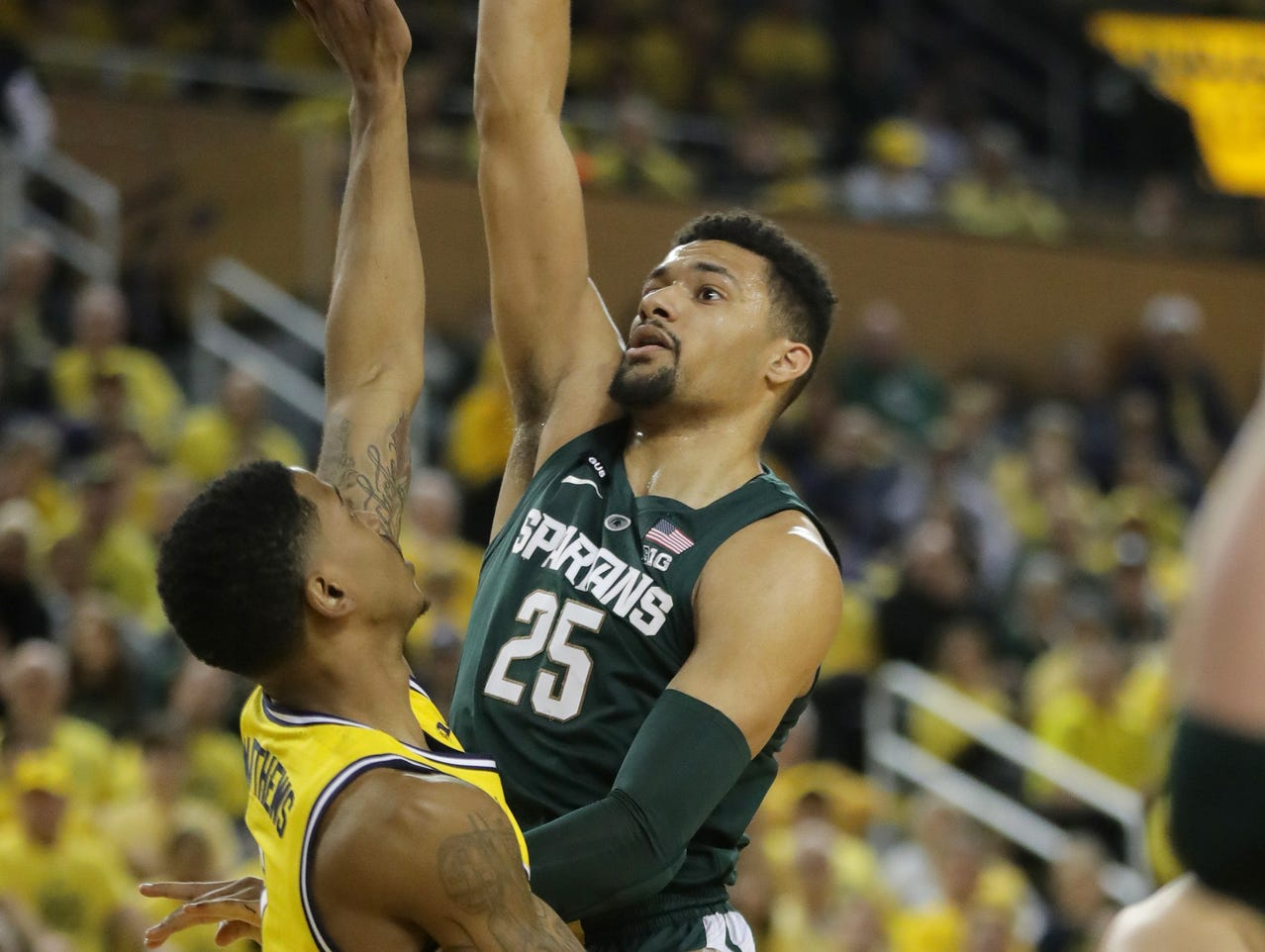 Michigan State forward Kenny Goins scores against Michigan guard Charles Matthews during the first half on Sunday, February 24, 2019 at the Crisler Center in Ann Arbor.