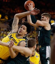 Michigan State forward Kyle Ahrens (0) grabs a rebound next to Michigan forward Brandon Johns Jr. during the first half of an NCAA college basketball game, Sunday, Feb. 24, 2019, in Ann Arbor, Mich. (AP Photo/Carlos Osorio)