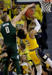 MSU's Kyle Ahrens blocks a shot by Michigan's Jordan Poole during the first half Sunday at the Crisler Center in Ann Arbor.