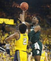 Aaron Henry shoots against Jordan Poole in the first half.