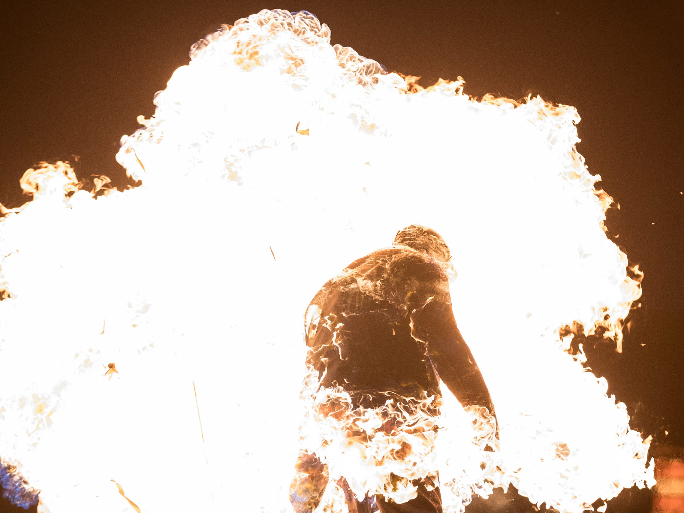 Stuntman Schuyler White runs into balloons filled with explosives after he attempts to break the World Record of most consecutive jumping jacks with full-body burn at the Veterans Park in Hamtramck, Saturday, Feb. 23, 2019. The world record is 30, White finished with 12 jumps.