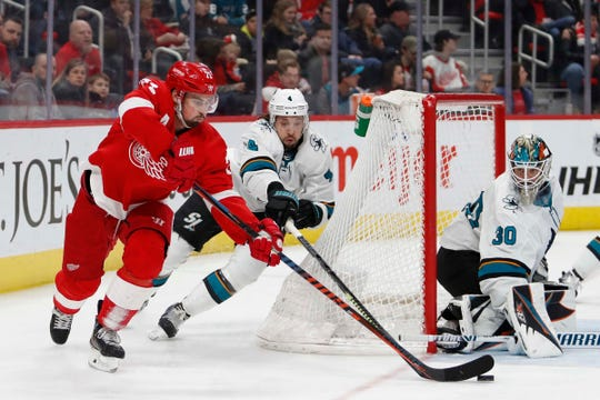 Red Wings center Dylan Larkin attempts a shot against Sharks goaltender Aaron Dell as he is defended by defenseman Brenden Dillon during the second period of the Wings' 5-3 loss on Sunday, Feb. 24, 2019, at Little Caesars Arena.