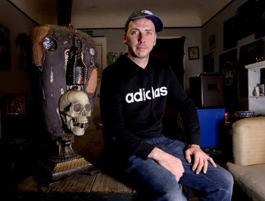 Matthew Urquhart, of Royal Oak, with his work of scrap lamp art that's in his father's house in Pontiac, Michigan on Saturday, February 23, 2019. Urquhart is a junk artist and scrapper who created the lamp base from discarded items including a Harley Davidson gas tank and a toy skull for the piece.