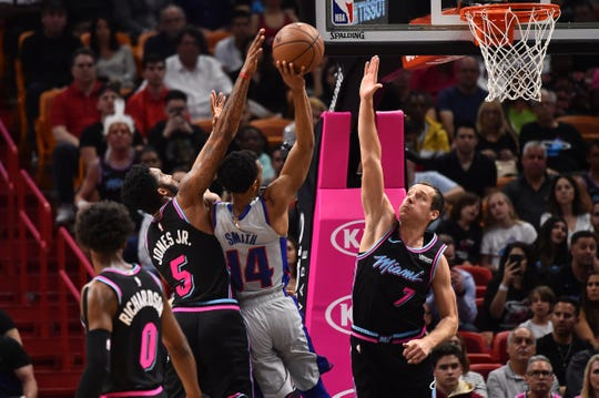Detroit Pistons guard Ish Smith (14) shoots between Miami Heat forward Derrick Jones Jr. (5) and guard Goran Dragic (7) during the first half at American Airlines Arena in Miami on Feb. 23, 2019.