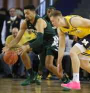 Michigan State's Kenny Goins goes for the lose ball against Michigan's Ignas Brazdeikis during the first half Sunday, Feb. 24, 2019 at the Crisler Center in Ann Arbor.