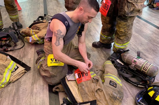 Michael Khoury, a firefighter for the Hazel Park Fire Department, readies his gear as he prepares to climb up to the 28th floor of the One Woodward building and back down on Sunday, Feb. 24 as part of the American Lung Association Fight for Air.
