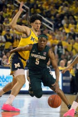 Michigan State guard Cassius Winston drives against Michigan forward Brandon Johns Jr. during the first half on Sunday, February 24, 2019 at the Crisler Center in Ann Arbor.