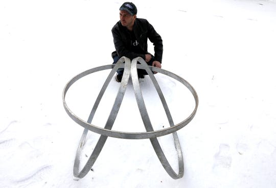 Matthew Urquhart of Royal Oak outside his father's house in Pontiac, Michigan on Saturday, February 23, 2019 with three rings he found and turned into an art sculpture. Urquhart is all for people reclaiming throwing away items and doesn't understand why some cities like Royal Oak have laws on the books against such a thing.