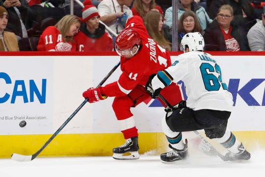 Red Wings right wing Filip Zadina gets defended by Sharks right wing Kevin Labanc during the second period of the Wings' 5-3 loss Sunday, Feb. 24, 2019, at Little Caesars Arena.