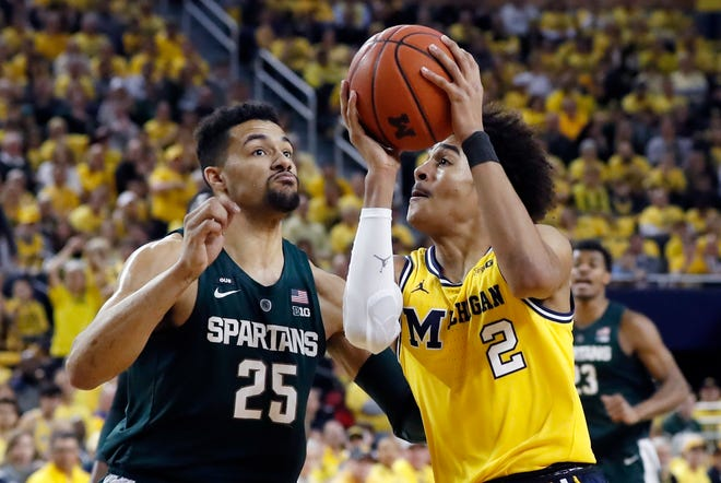 Michigan guard Jordan Poole is defended by Michigan State forward Kenny Goins during the first half Sunday, Feb. 24, 2019, in Ann Arbor.