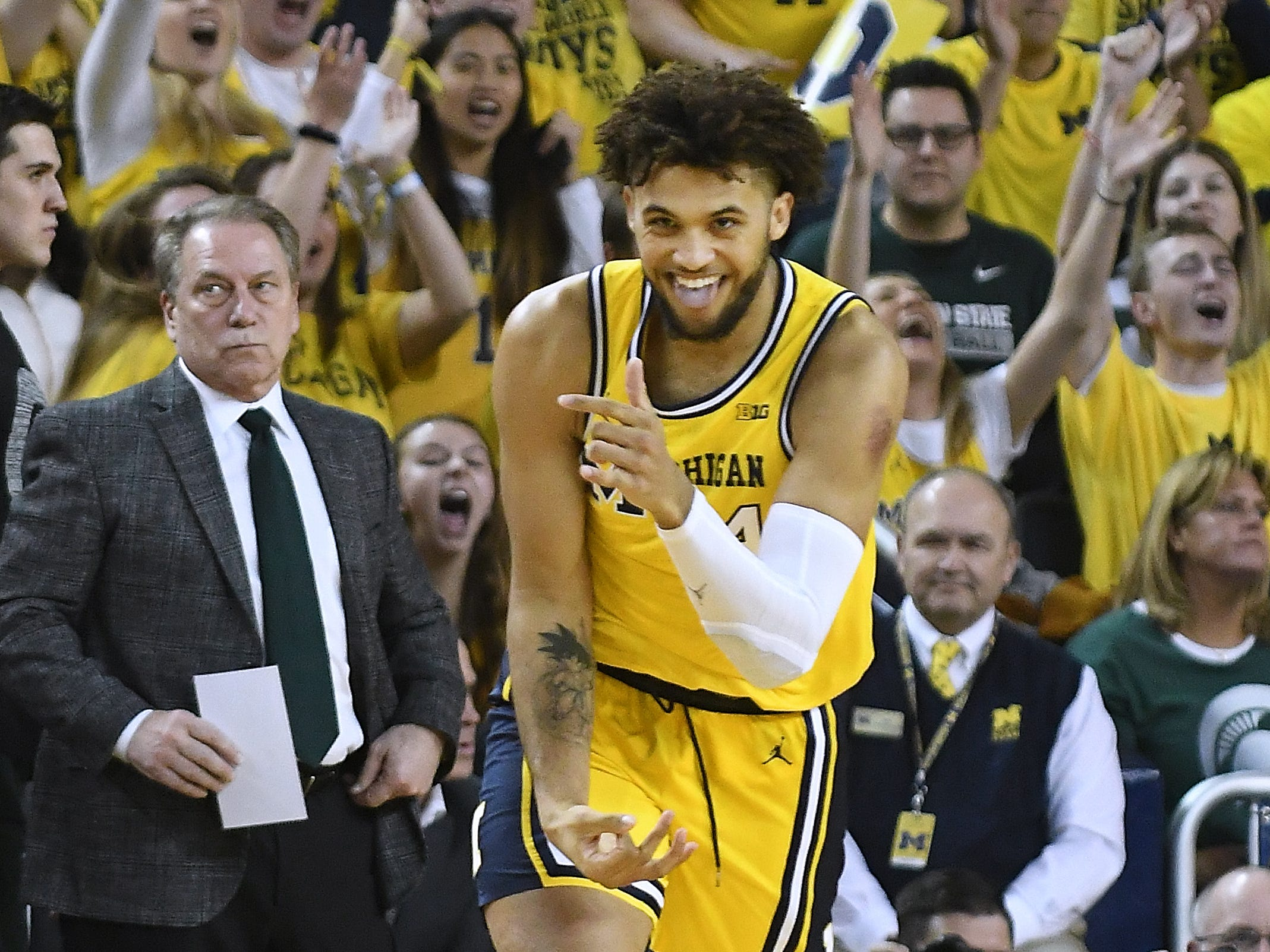 Michigan's Isaiah Livers celebrates after hitting a first-half basket with Michigan State head coach Tom Izzo looking on in the background.