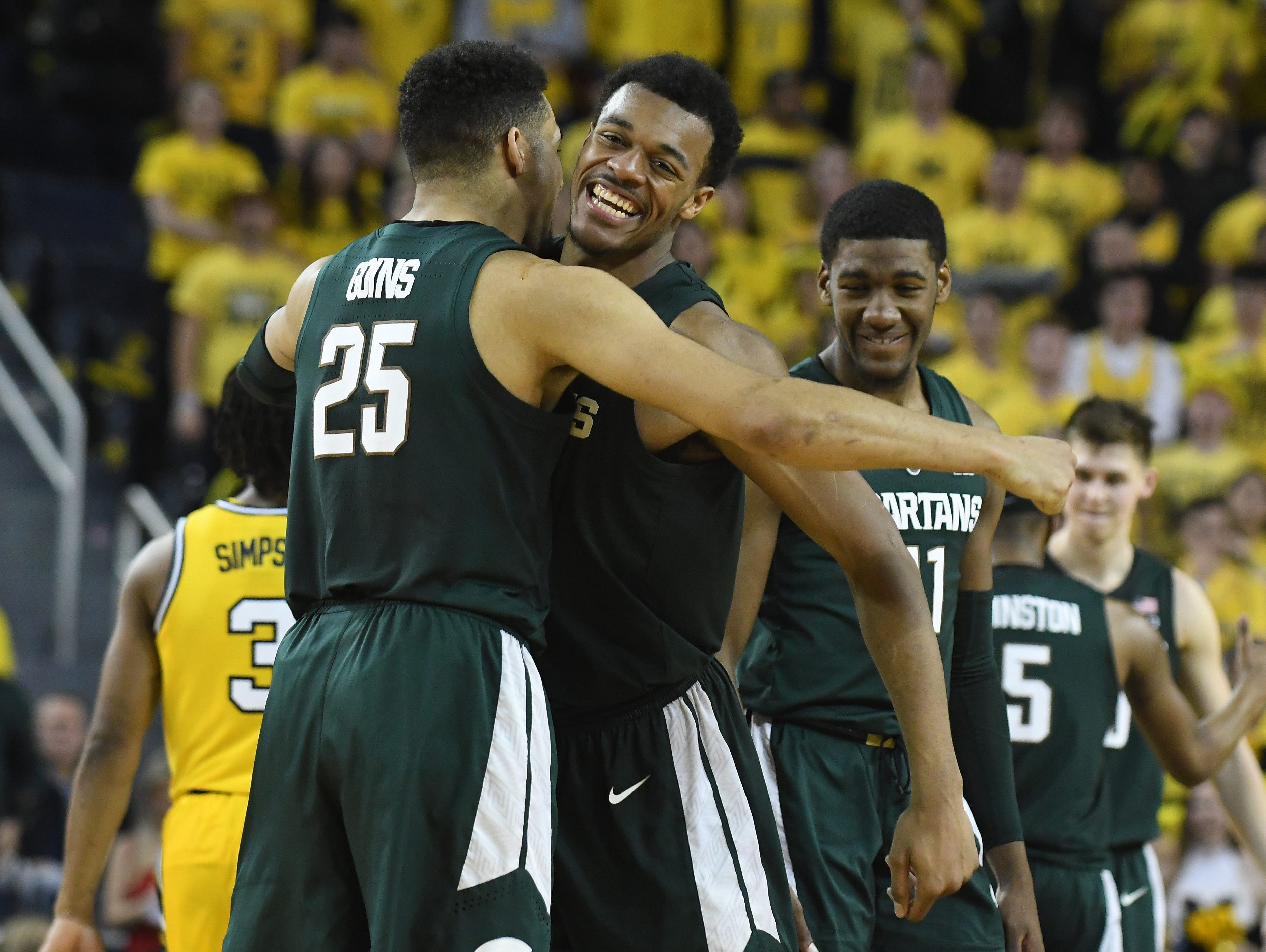 Michigan State players Kenny Goins, Xavier Tillman (facing) and Aaron Henry begin to celebrate as the clock ticks down on a 77-70 Spartans' road victory over Michigan at Crisler Center in Ann Arbor on Sunday February 24, 2019.