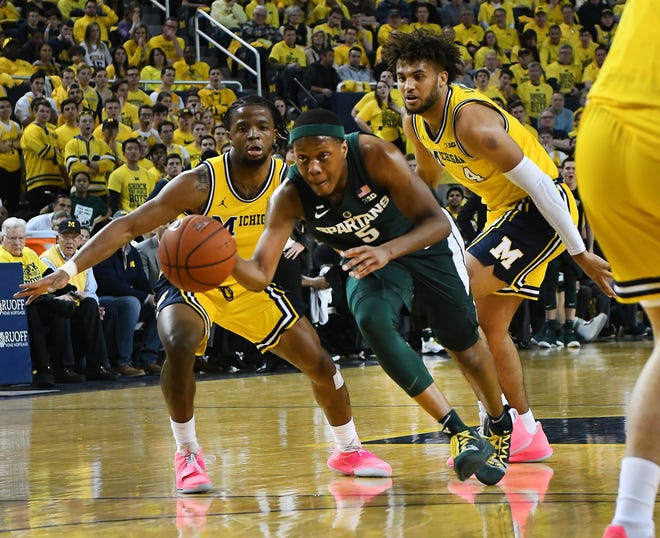 Michigan State's Cassius Winston splits Michigan's Zavier Simpson and Isaiah Livers in the first half.