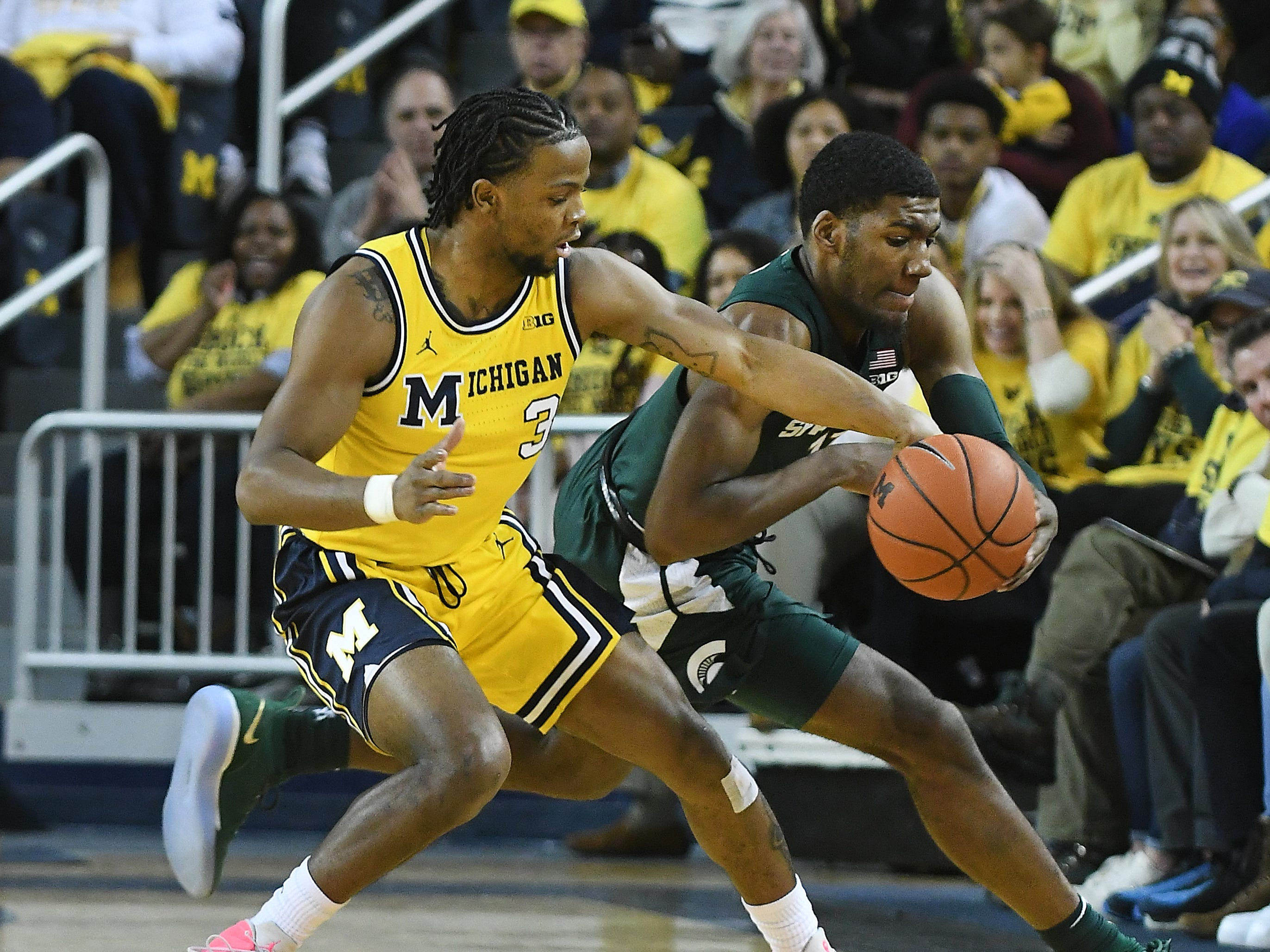 Michigan's Zavier Simpson and Michigan State's Aaron Henry battle for a loose ball in the first half.