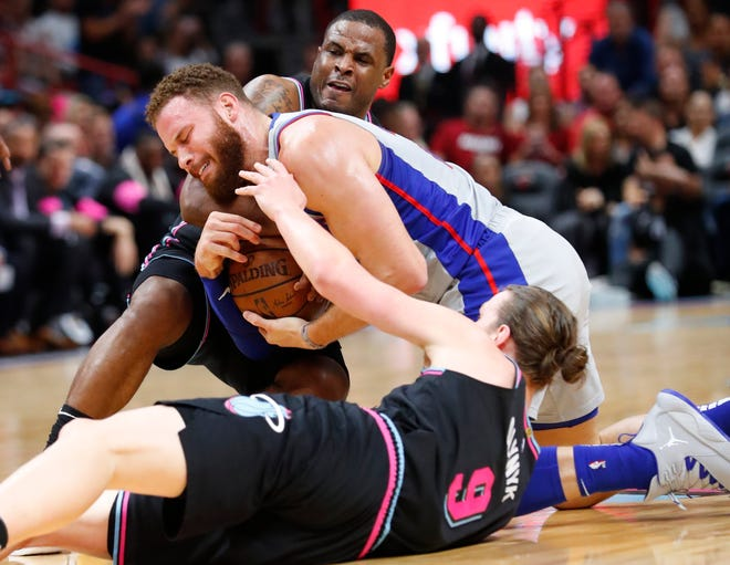 Miami Heat forward Kelly Olynyk (9) and guard Dion Waiters, rear, battle for the ball with Detroit Pistons forward Blake Griffin.