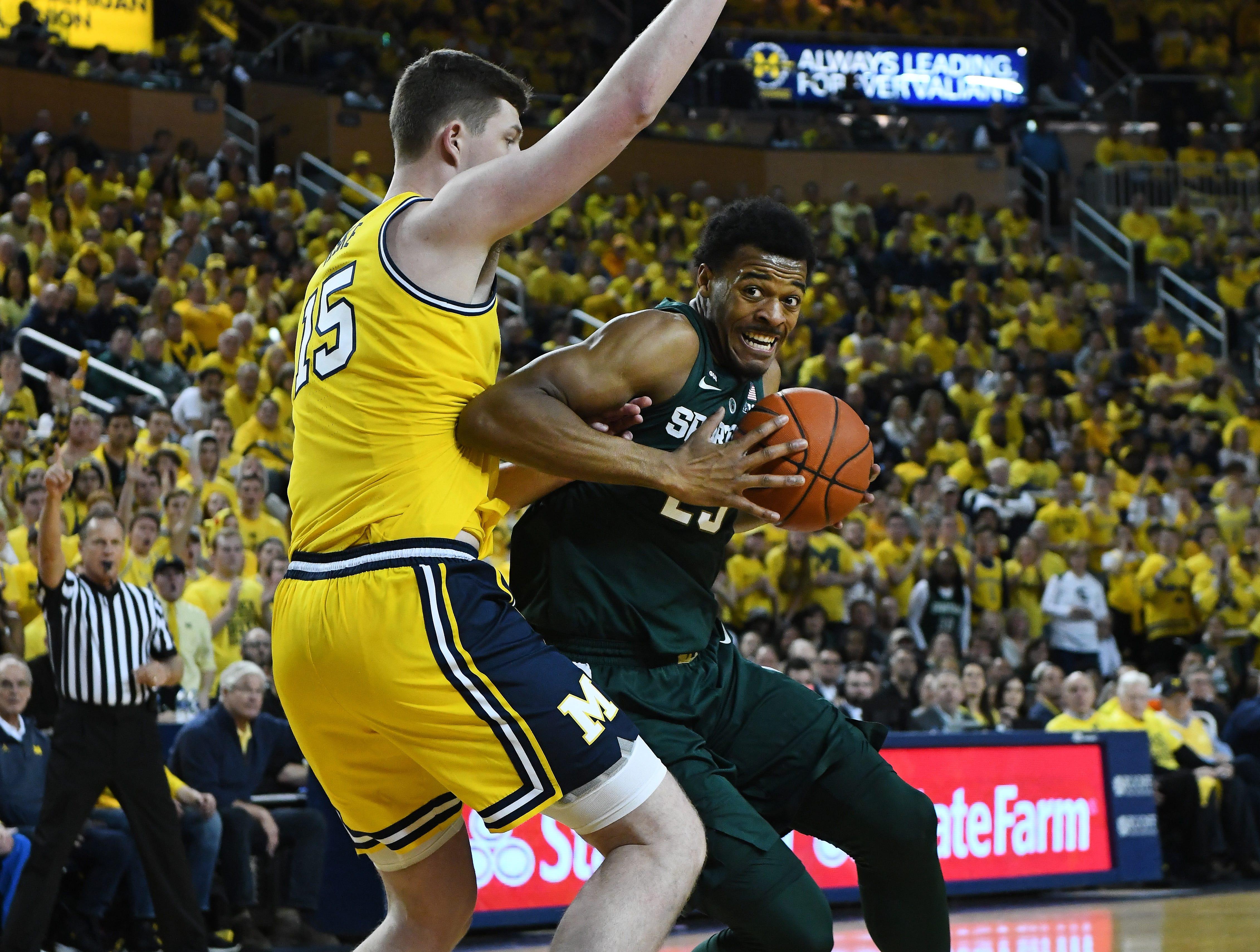 Michigan's Jon Teske, left, defends against Michigan State's Xavier Tillman under the basket in the first half.