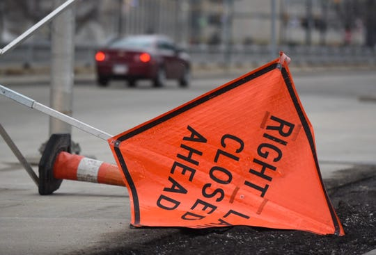 Motorists maneuver around obstacles as high winds toppled a road caution sign along Jefferson Avenue in downtown Detroit on Sunday, February 24, 2019.
