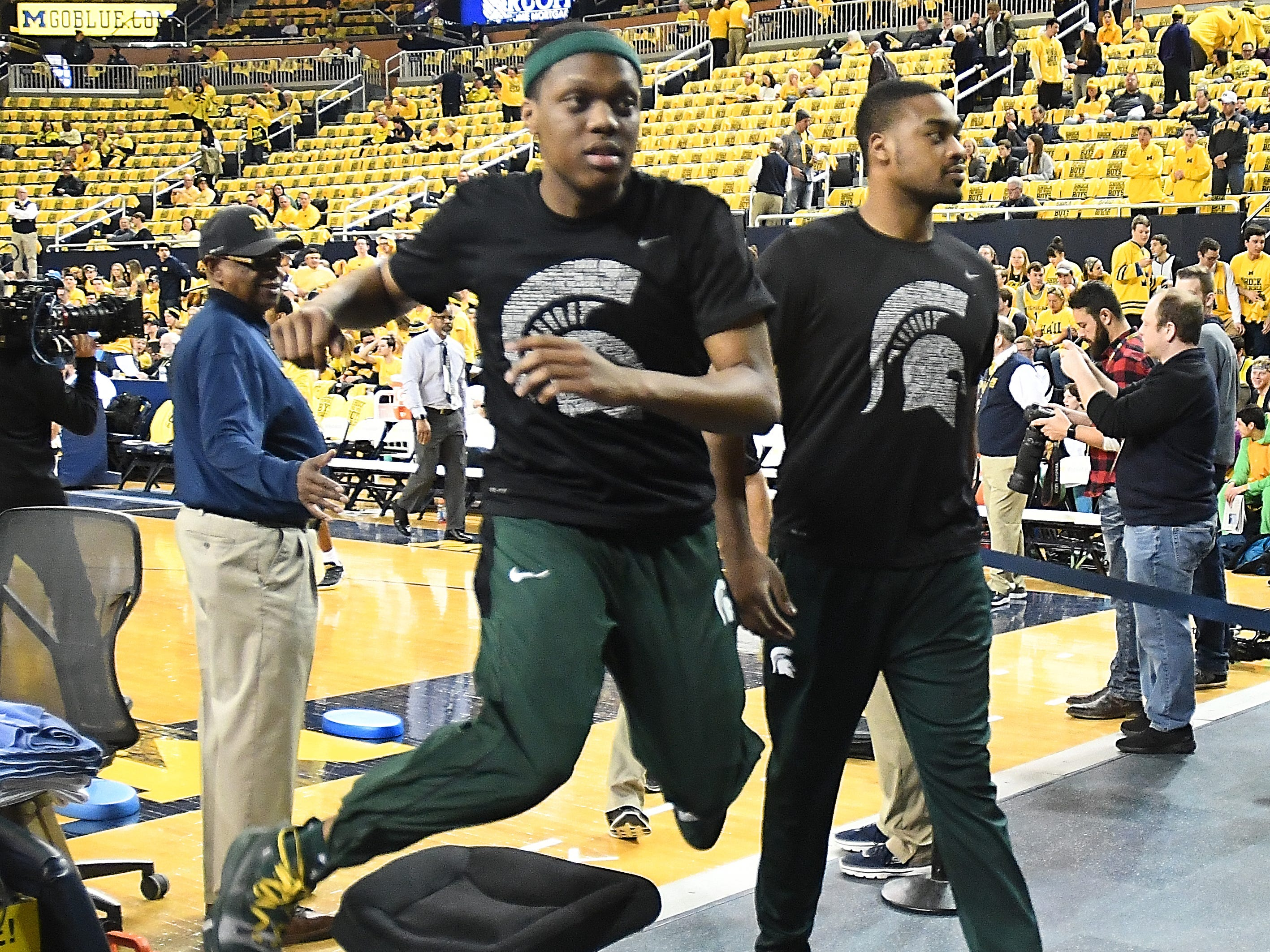 Michigan State's Cassius Winston leaps over a chair as he and injured Nick Ward leave the court after warmups.