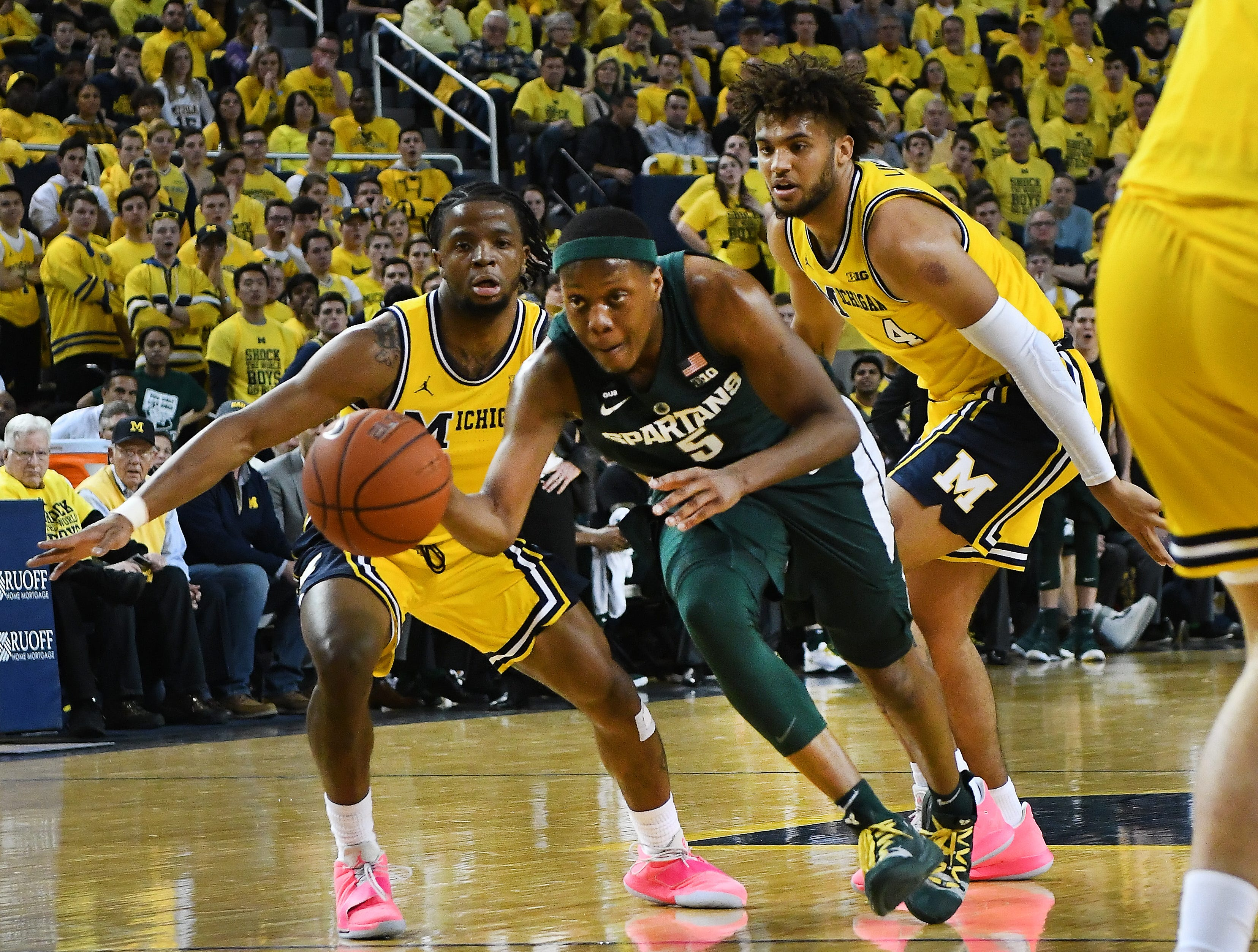 Michigan State's Cassius Winston splits Michigan defenders Zavier Simpson, left, and Isaiah Livers while driving to the basket in the first half at Crisler Center in Ann Arbor, Michigan on February 24, 2019.