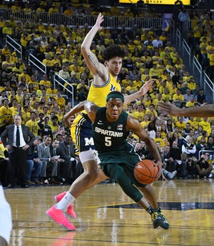 Michigan's Brandon Johns Jr. can't stop Michigan State's Cassius Winston from driving to the basket in the first half.