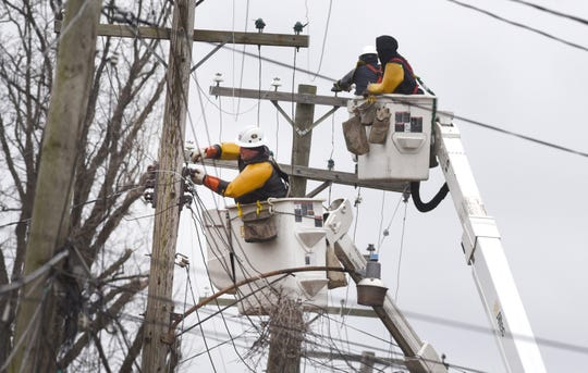 DTE line crews repair a power line along Caniff Street near Oakland Street in Detroit on Sunday, February 24, 2019 as high winds caused power outages in the area.
