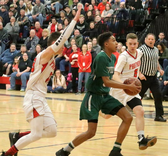 Daejahd Leckey of Newfield drives to the basket between Spencer-Van Etten's Noah Mack, left, and Brian Gillette during a Section 4 Class C boys quarterfinal on Feb. 23, 2019 at S-VE.