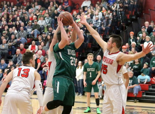 Kade Pawlewicz of Newfield looks for room in the paint as Spencer-Van Etten's Noah Mack (13) and Nathan Mack (15) defend during a Section 4 Class C boys quarterfinal on Feb. 23, 2019 at S-VE.