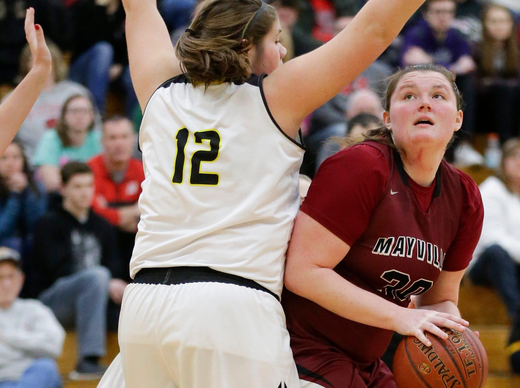 Waupun High School girls basketball's Kelli Bonack (12) defends Mayville High School's Sydney Schultz (30) Saturday, February 23, 2019 during their WIAA Division 4 sectional quarterfinal game in Waupun. Waupun won the game 62-45. Doug Raflik/USA TODAY NETWORK-Wisconsin