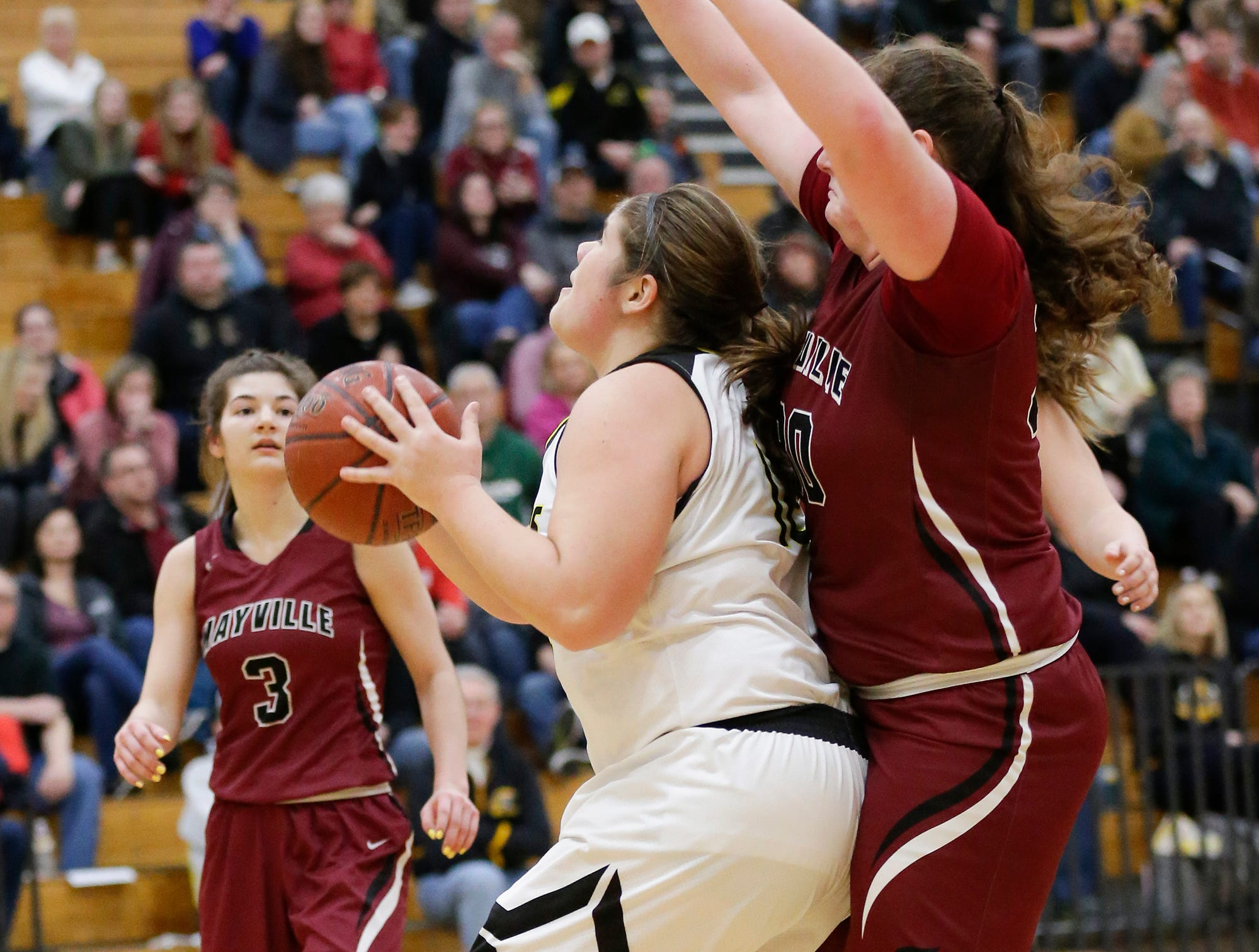 Waupun High School girls basketball's Kelli Bonack (12) eyes up a shot while being defended by Mayville High School's Sydney Schultz (30) Saturday, February 23, 2019 during their WIAA Division 4 sectional quarterfinal game in Waupun. Waupun won the game 62-45. Doug Raflik/USA TODAY NETWORK-Wisconsin