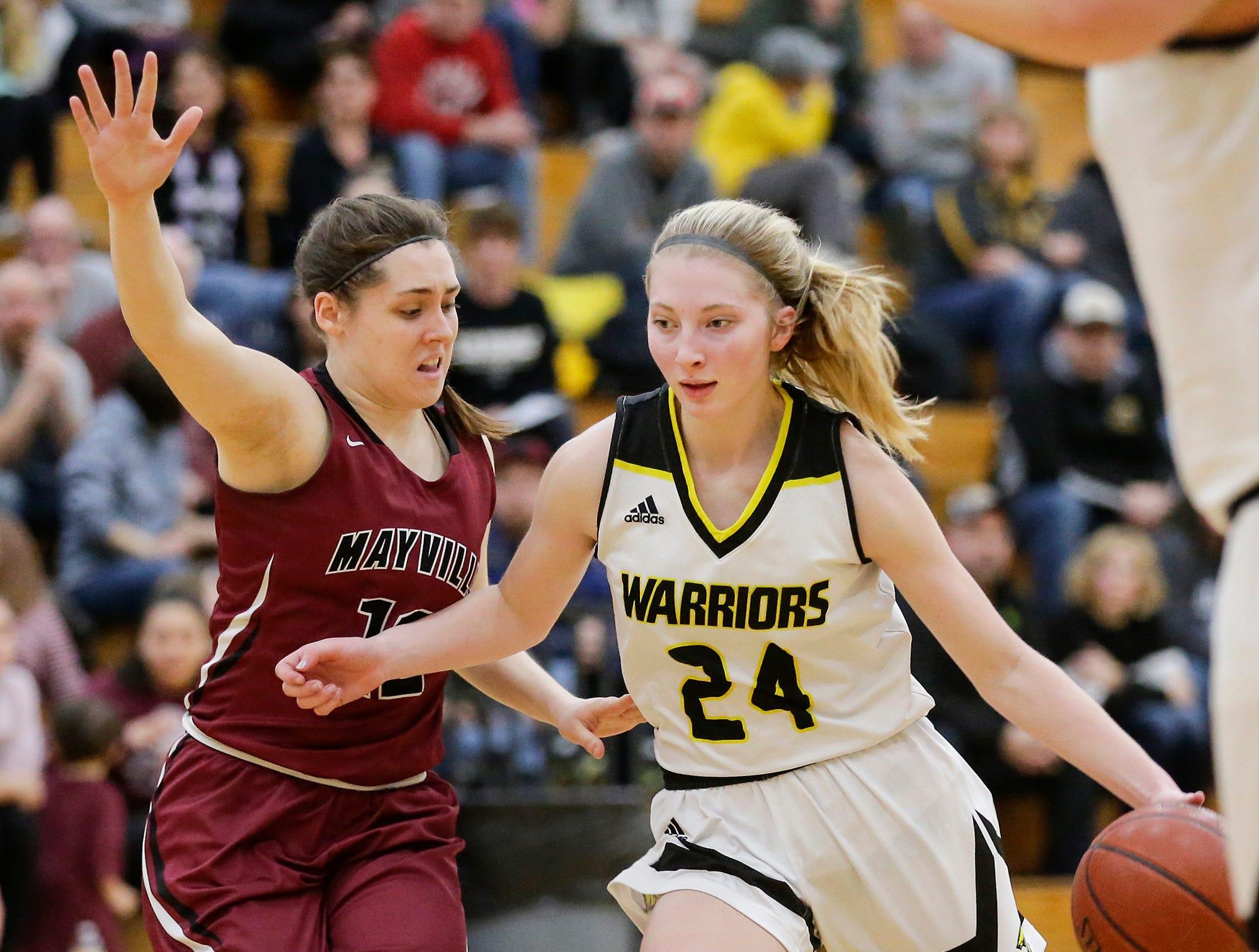 Waupun High School girls basketball's Peyton McGinnis (24) works her way past Mayville High School's Alaina Wagner (12) Saturday, February 23, 2019 during their WIAA Division 4 sectional quarterfinal game in Waupun. Waupun won the game 62-45. Doug Raflik/USA TODAY NETWORK-Wisconsin