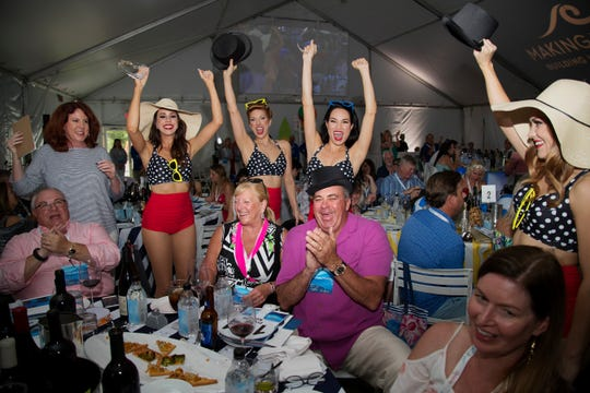 Sheree Kent, center, and husband Michael celebrate a winning auction bid at the Southwest Florida Wine & Food Fest this year at the Hyatt Regency Coconut Point Resort in in Bonita Springs. The annual event supports programs addressing children's mental and behavioral health needs.