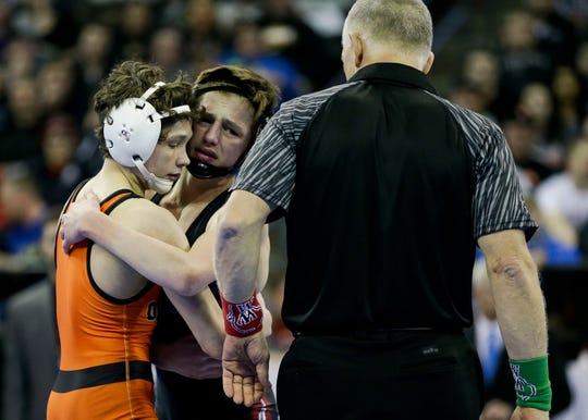 Winneconne's Caleb Meunier congratulates Stanley-Boyd/Owen-Withee's Blaine Brenner after the Division 2 106-pound championship match Saturday during the WIAA state wrestling tournament at the Kohl Center in Madison.