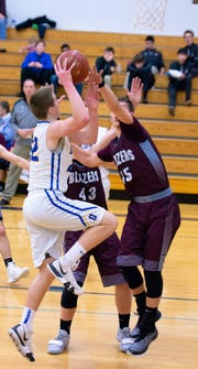 Oconto';s Caleb Moe scores over Adam Gosse (43) and Sam Meerstein (15) in the first half of the game against NEW Lutheran on Feb 18 in Oconto.