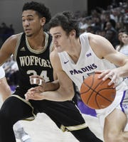 Furman's Clay Mounce (45) drives by Wofford's Keve Aluma (24) Saturday at Timmons Arena.
