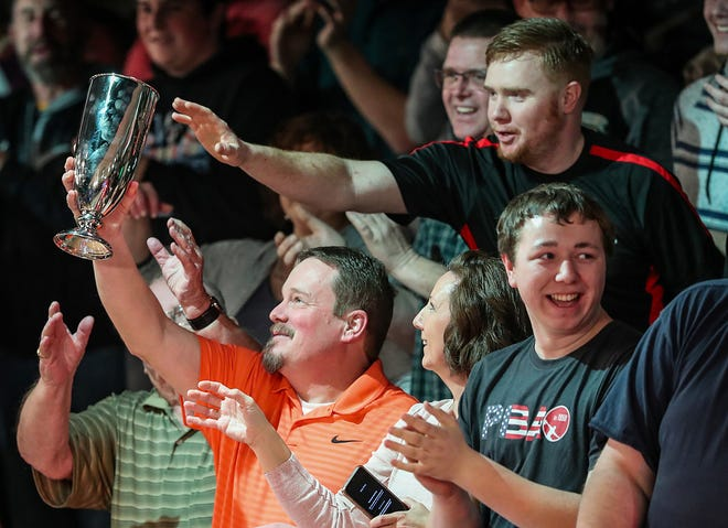 Fans pass around the trophy earned by Norm Duke in the Go Bowling! PBA Indianapolis Open at Woodland Bowl in Indianapolis on Sunday, Feb. 24, 2019. Norm Duke defeated Jason Belmonte, 237-219, to earn his 39th career title.