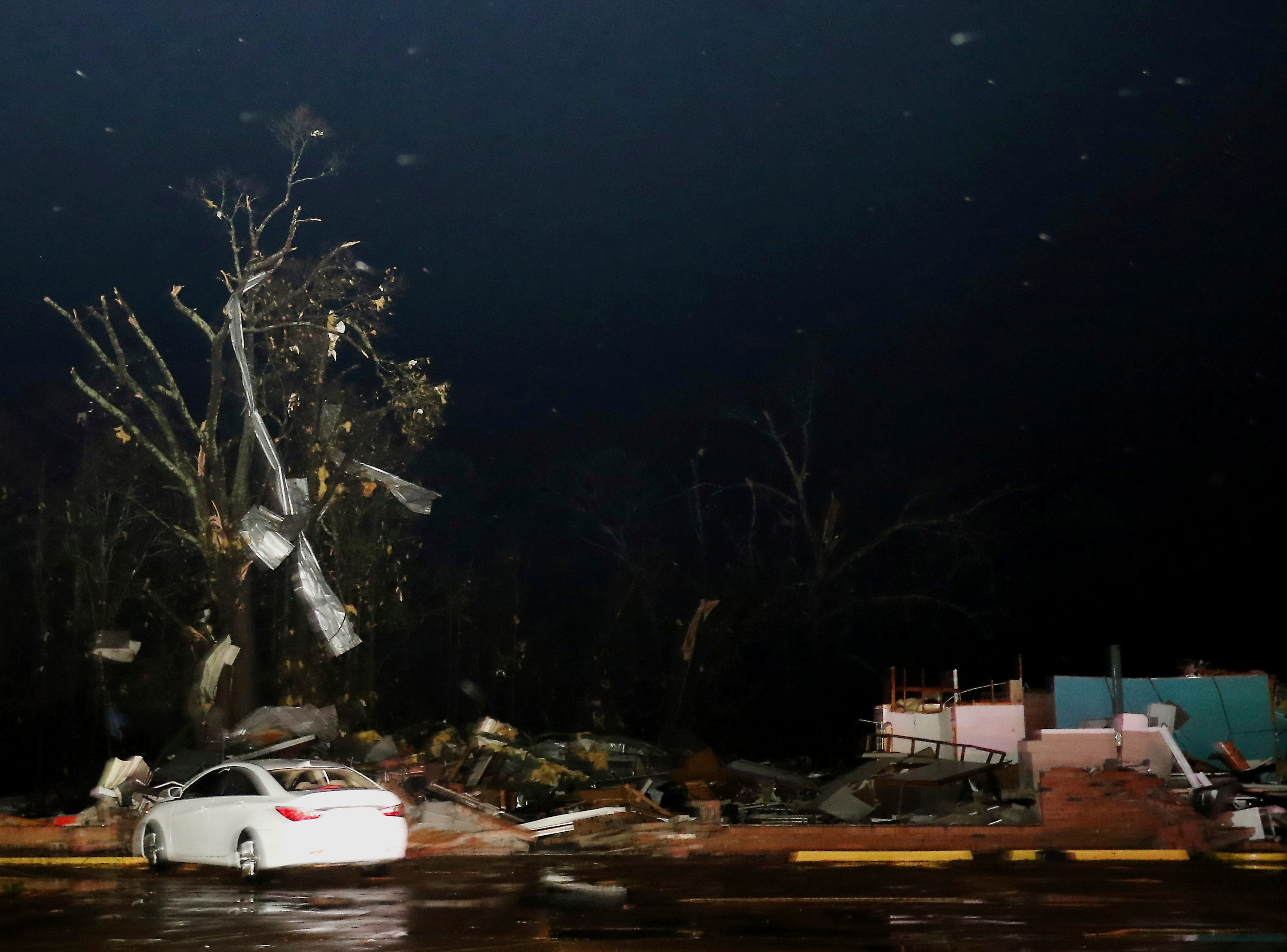 Tin from nearby buildings sits in a tree above a destroyed vacant commercial structure along highway 50 in Columbus, Miss., after a tornado struck the area on Saturday, Feb. 23, 2019. (AP Photo/Jim Lytle)