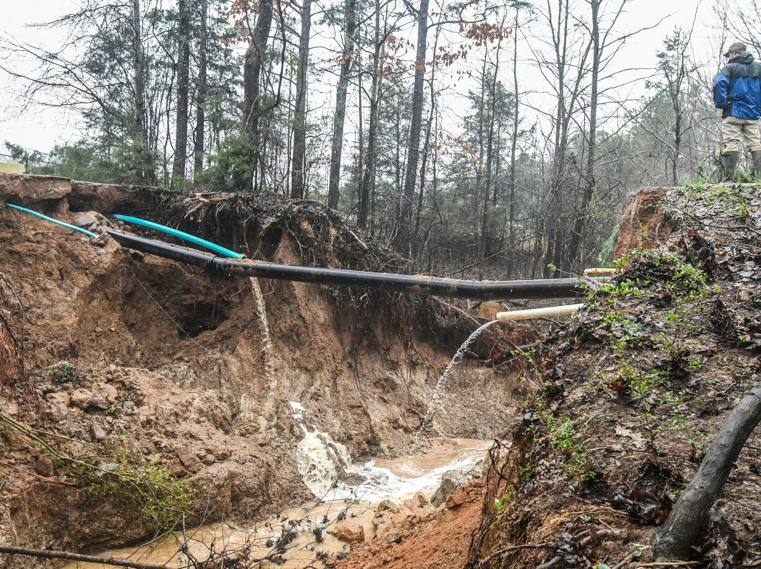 Hunter Maples looks over a water line break caused by heavy rainfall near the Max Hipp Industrial Park in Oxford, Miss. on Saturday, Feb. 23, 2019. The city of Oxford has issued a self-imposed precautionary boil-water notice for all customers that receive water from the city of Oxford, including those customers outside the city limits. (Bruce Newman/The Oxford Eagle via AP)