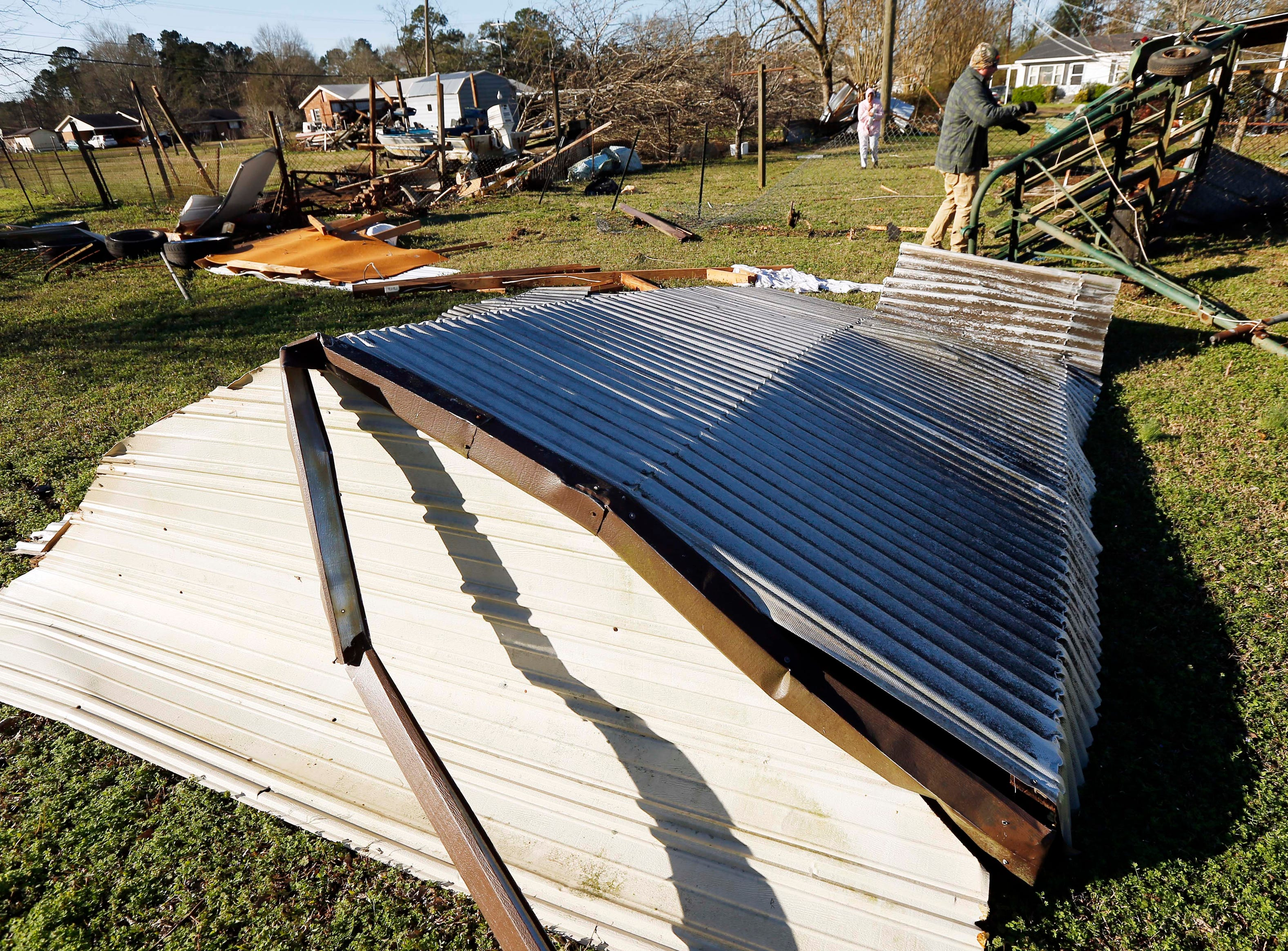 Tornado strewn debris, including this roofing, and fallen trees in this Columbus, Miss., neighborhood, Sunday morning, Feb. 24, 2019 after Saturday's tornado that killed at least one person and shattered businesses and several homes. (AP Photo/Rogelio V. Solis)