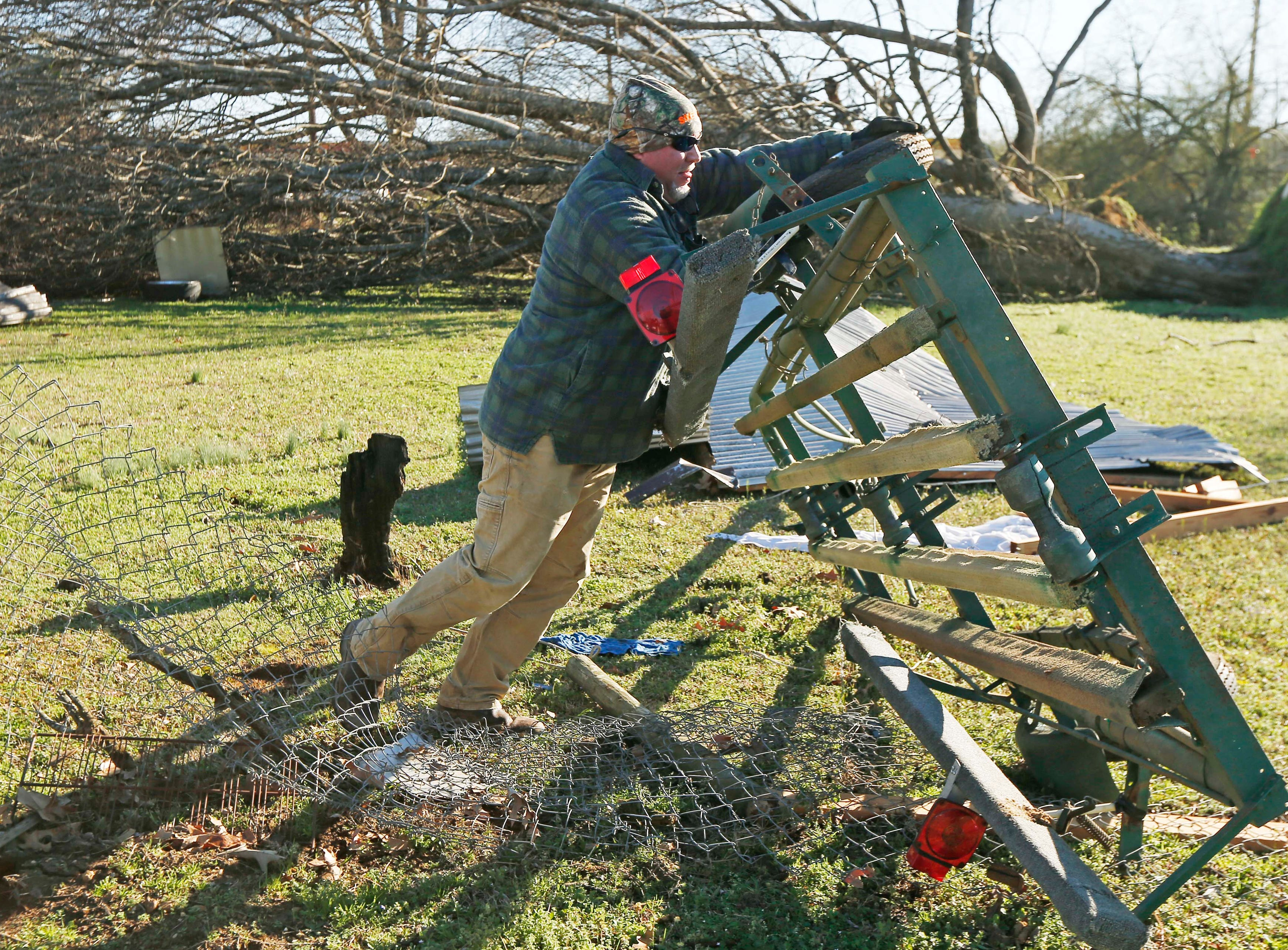Jack Gordman flips over a boat trailer that was tossed several feef from his parent's home in Columbus, Miss., Sunday morning, Feb. 24, 2019, after Saturday's tornado that killed at least one person and shattered businesses and several homes. (AP Photo/Rogelio V. Solis)