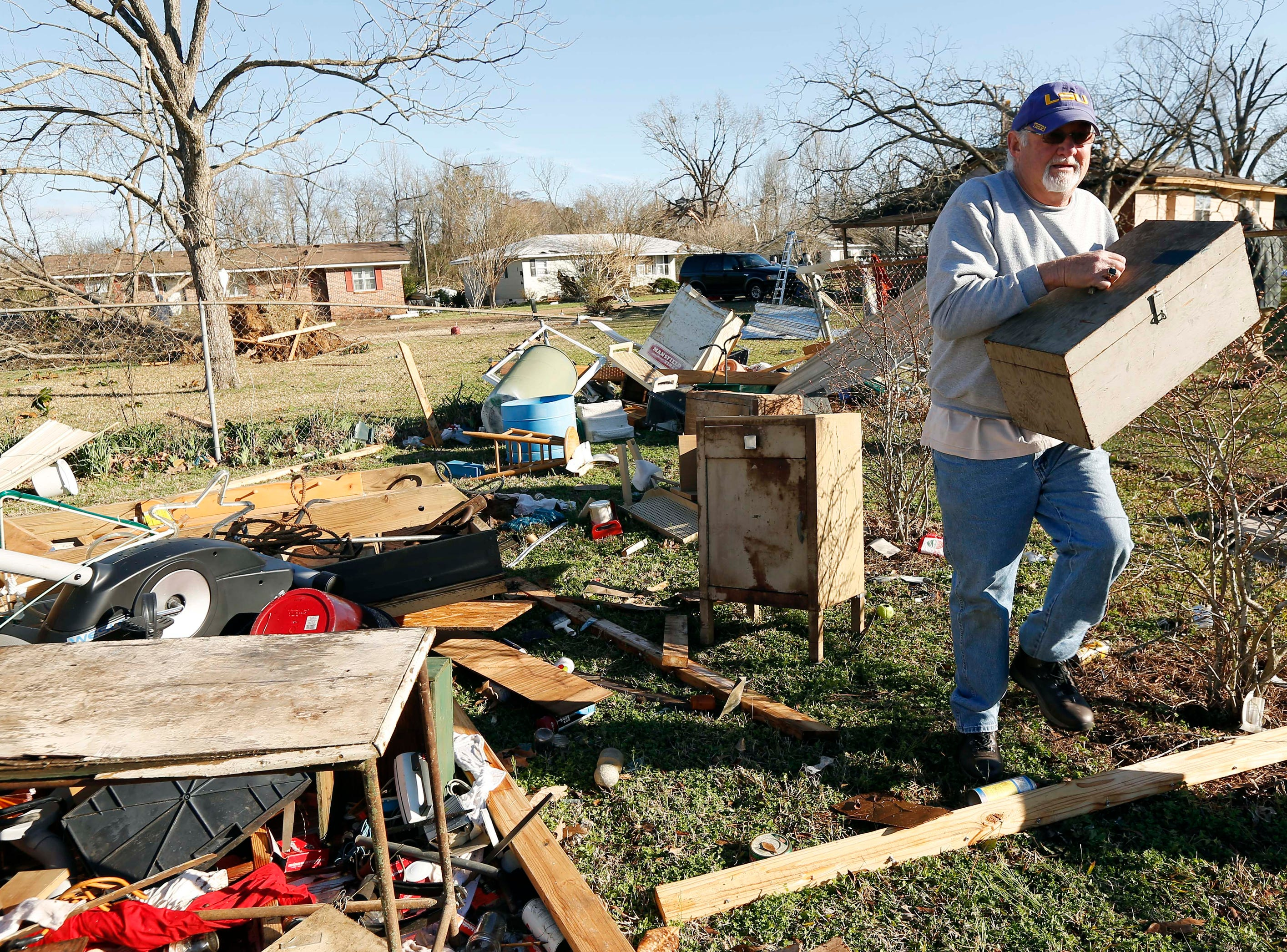 Al Bordelon salvages a tool box from what remains of his mother-in-law's shed in Columbus, Miss., Sunday morning, Feb. 24, 2019, after Saturday's tornado that killed at least one person and shattered businesses and several homes. (AP Photo/Rogelio V. Solis)