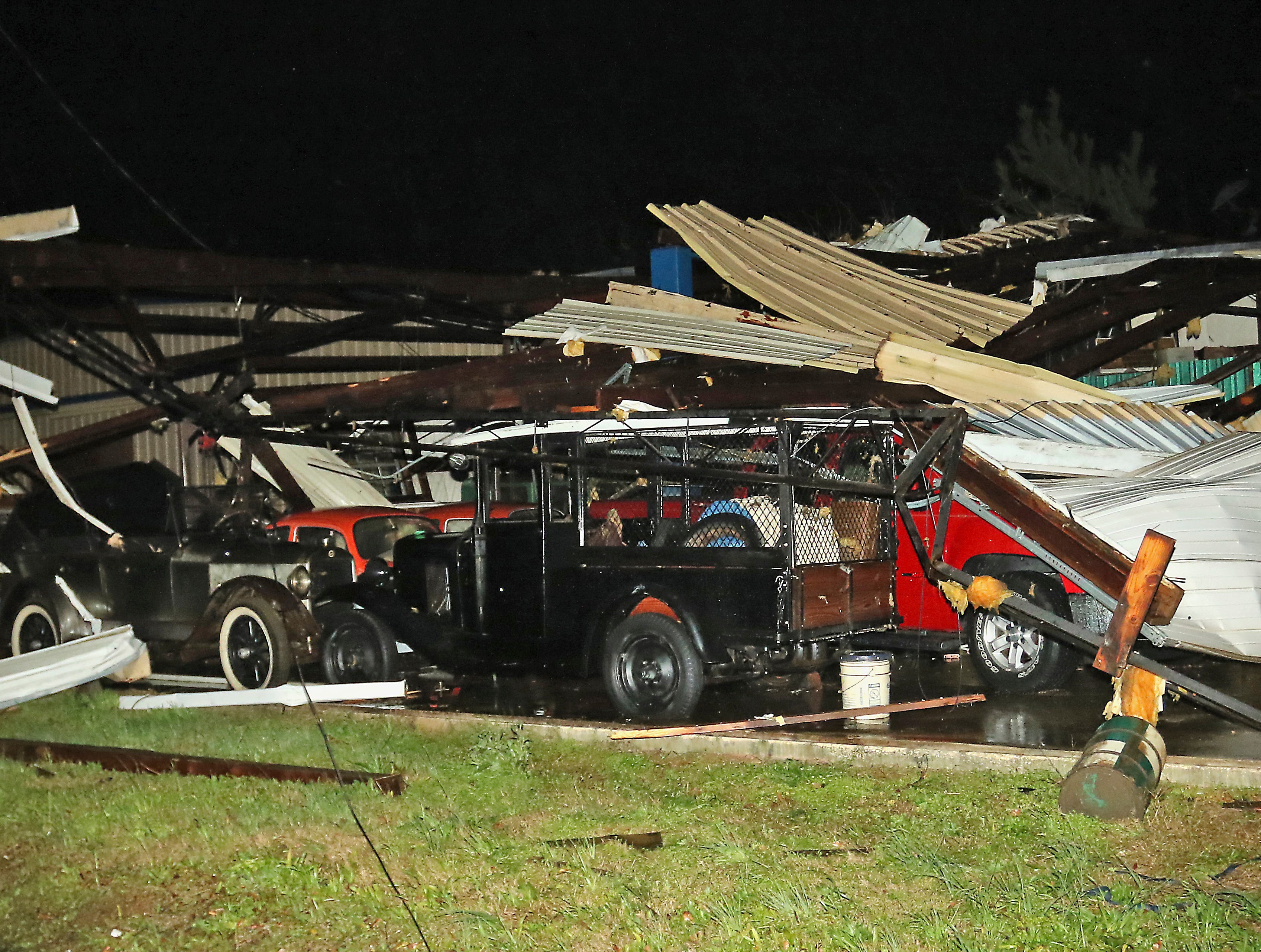 A 1923 Studebaker, left and a 1930 Chevrolet Paddy Wagon are exposed at Lawrence Motors along highway 50 in Columbus, Miss., after a tornado struck the area Saturday, Feb. 23, 2019. (AP Photo/Jim Lytle)