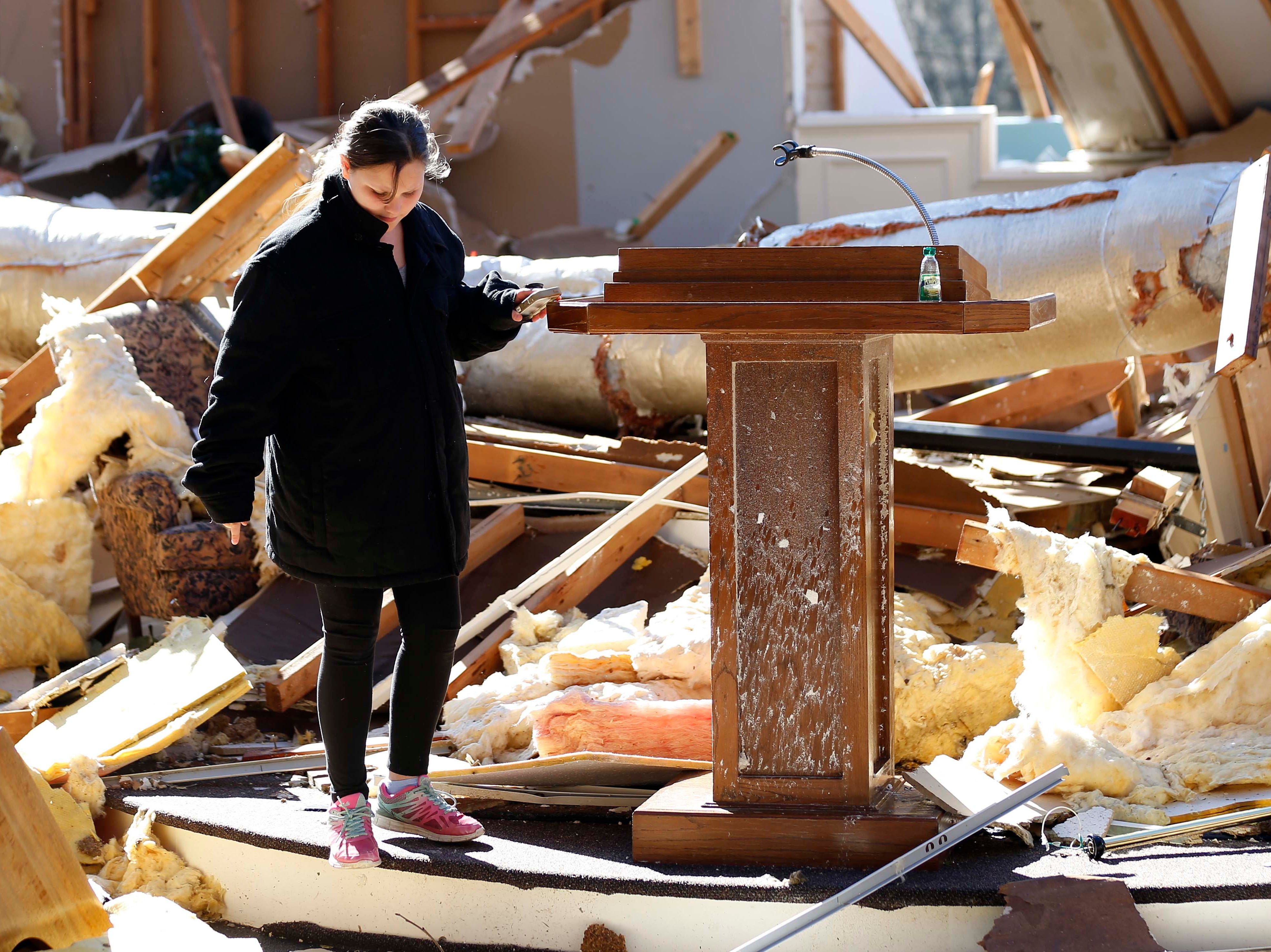 A child plays around the podium that was virtually undamaged or moved in the tornado that destroyed First Pentecostal Church in Columbus, Miss., Sunday morning, Feb. 24, 2019. While no-one was injured during Saturday's storm, at least one person was killed in town among the shattered businesses and wrecked homes. (AP Photo/Rogelio V. Solis)