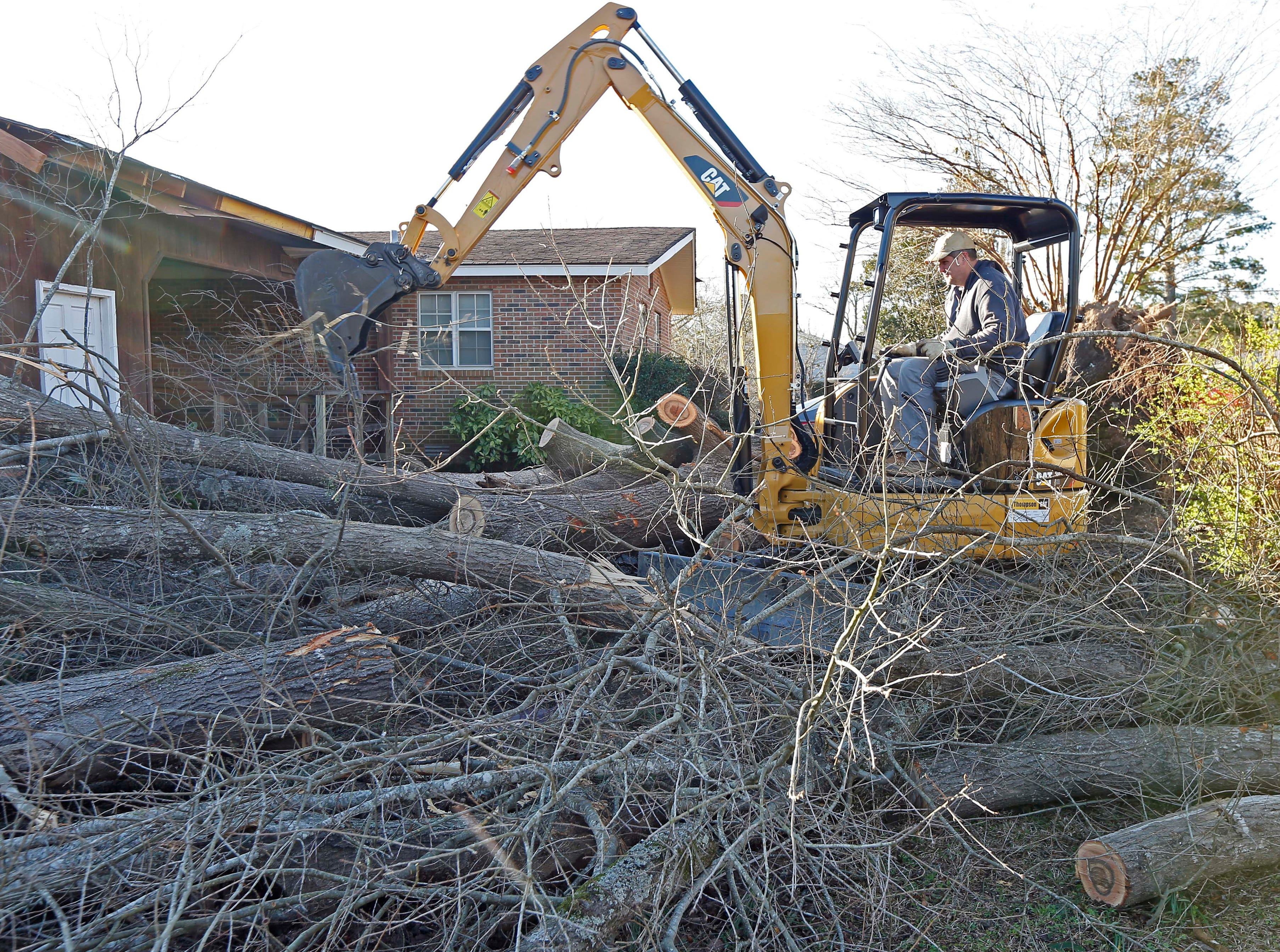 A backhoe is used to removes fallen tree limbs in this Columbus, Miss., neighborhood, Sunday morning, Feb. 24, 2019. At least one person was killed among the shattered businesses and wrecked homes that dotted the South as severe storms followed a weekend of drenching rains and a rising flood threat. (AP Photo/Rogelio V. Solis)