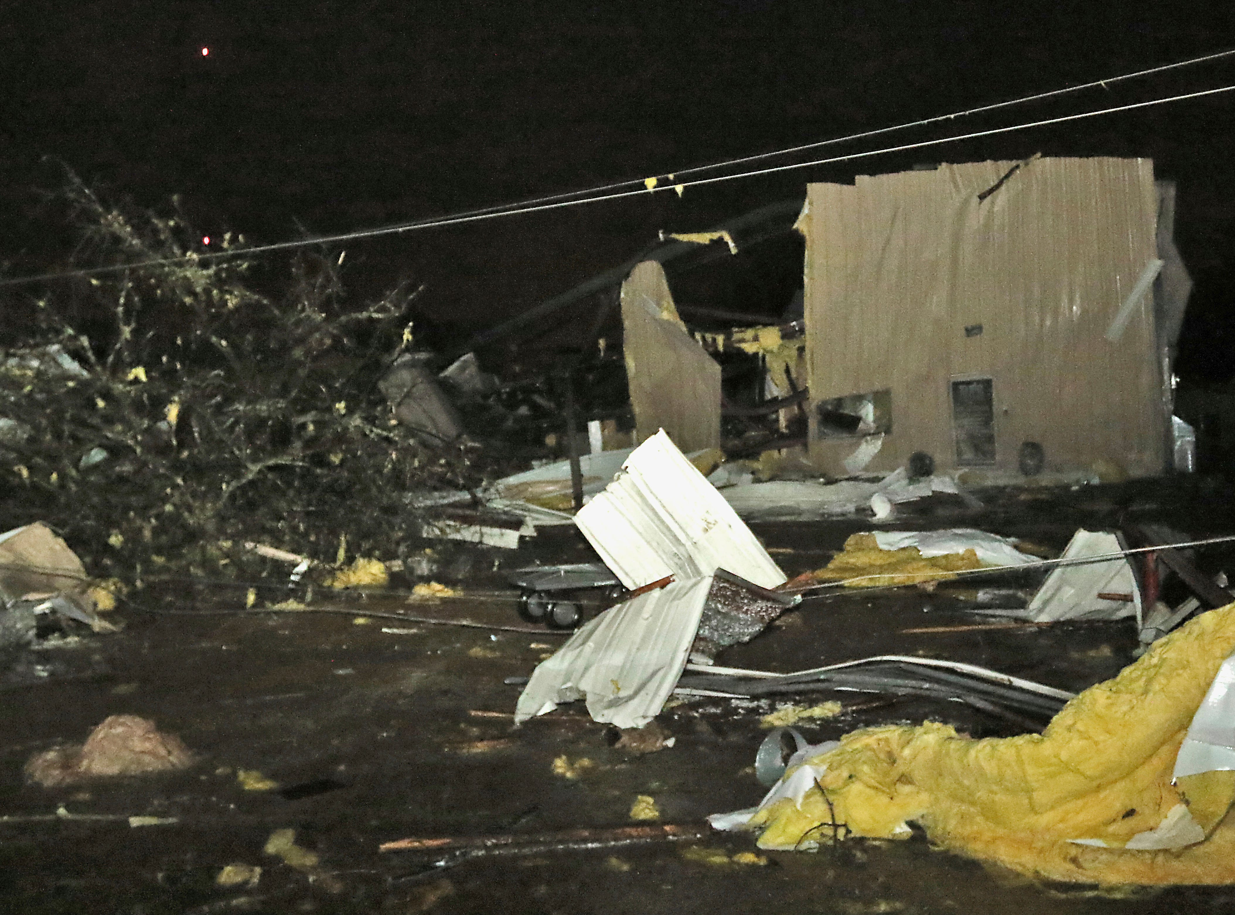 Downed power lines, trees and building debris from businesses including B.J.'s Dog Grooming liter Conway Drive in Columbus, Miss., after a tornado struck the area on Saturday, Feb. 23, 2019. (AP Photo/Jim Lytle)