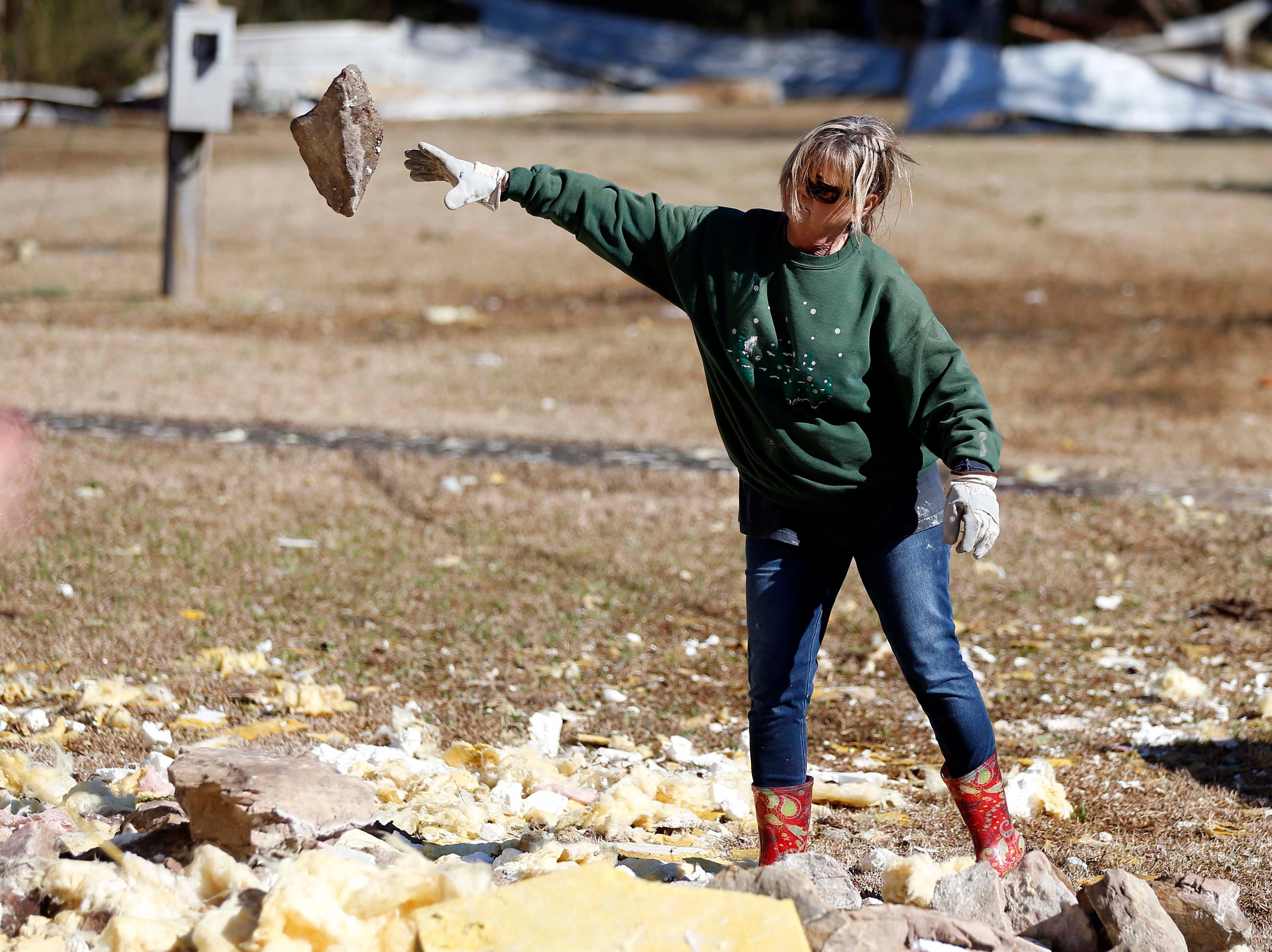 A church member tosses to the side a large stone that was part of the exterior of the First Pentecostal Church in Columbus, Miss., Sunday morning, Feb. 24, 2019. While no-one was injured during Saturday's storm, where at least one person was killed in town among the shattered businesses and wrecked homes. (AP Photo/Rogelio V. Solis)