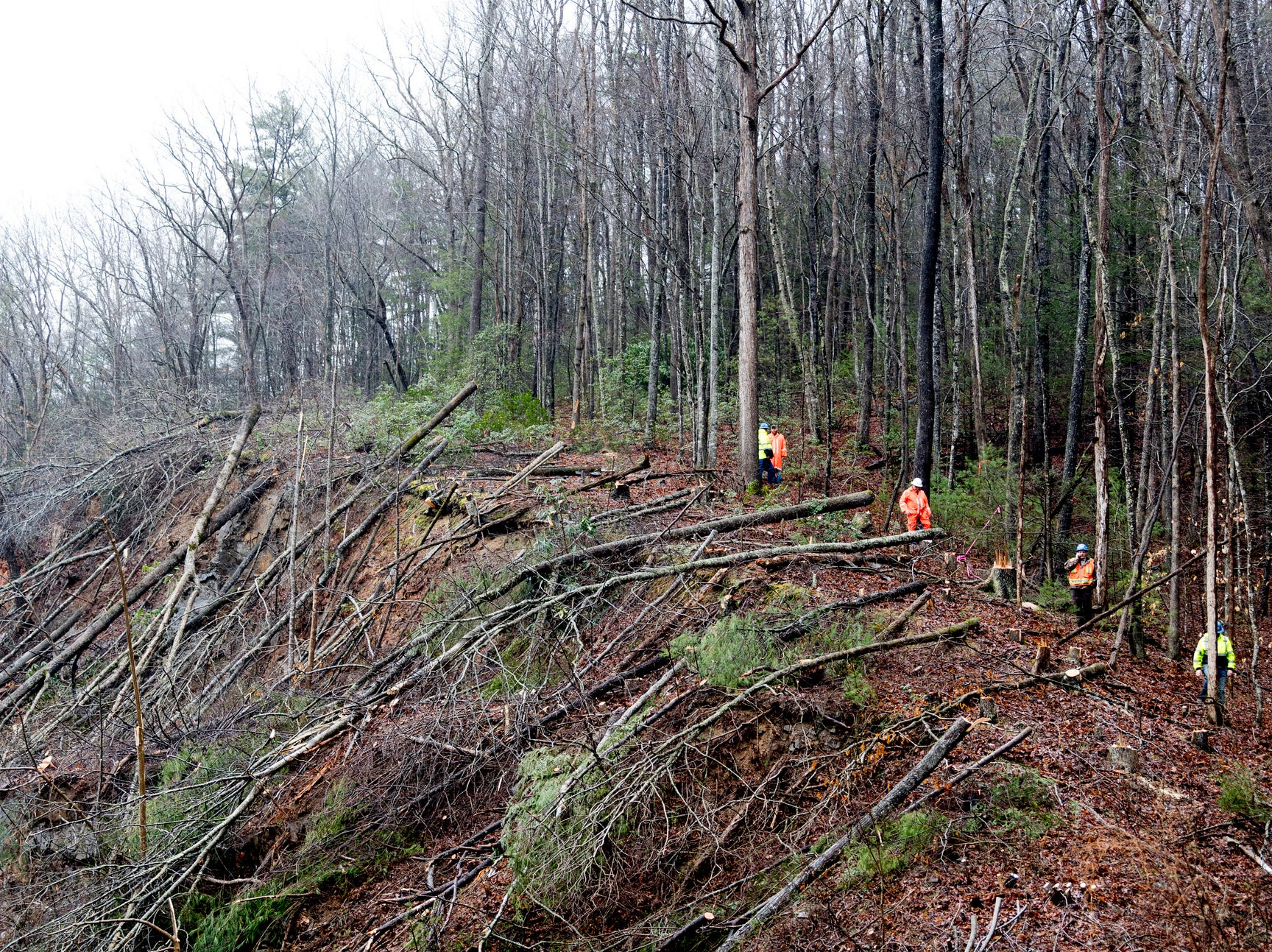 Workers climb along the edge of the mudslide on I-40 eastbound in Clyde, N.C., near the Tennessee and North Carolina border on Saturday, Feb. 23, 2019. Travel east and west on I-40 will be shut down for approximately four to seven days, with the east and west bound lanes to open with only one lane for around six weeks as crews continue repairs. (Calvin Mattheis/Knoxville News Sentinel via AP)