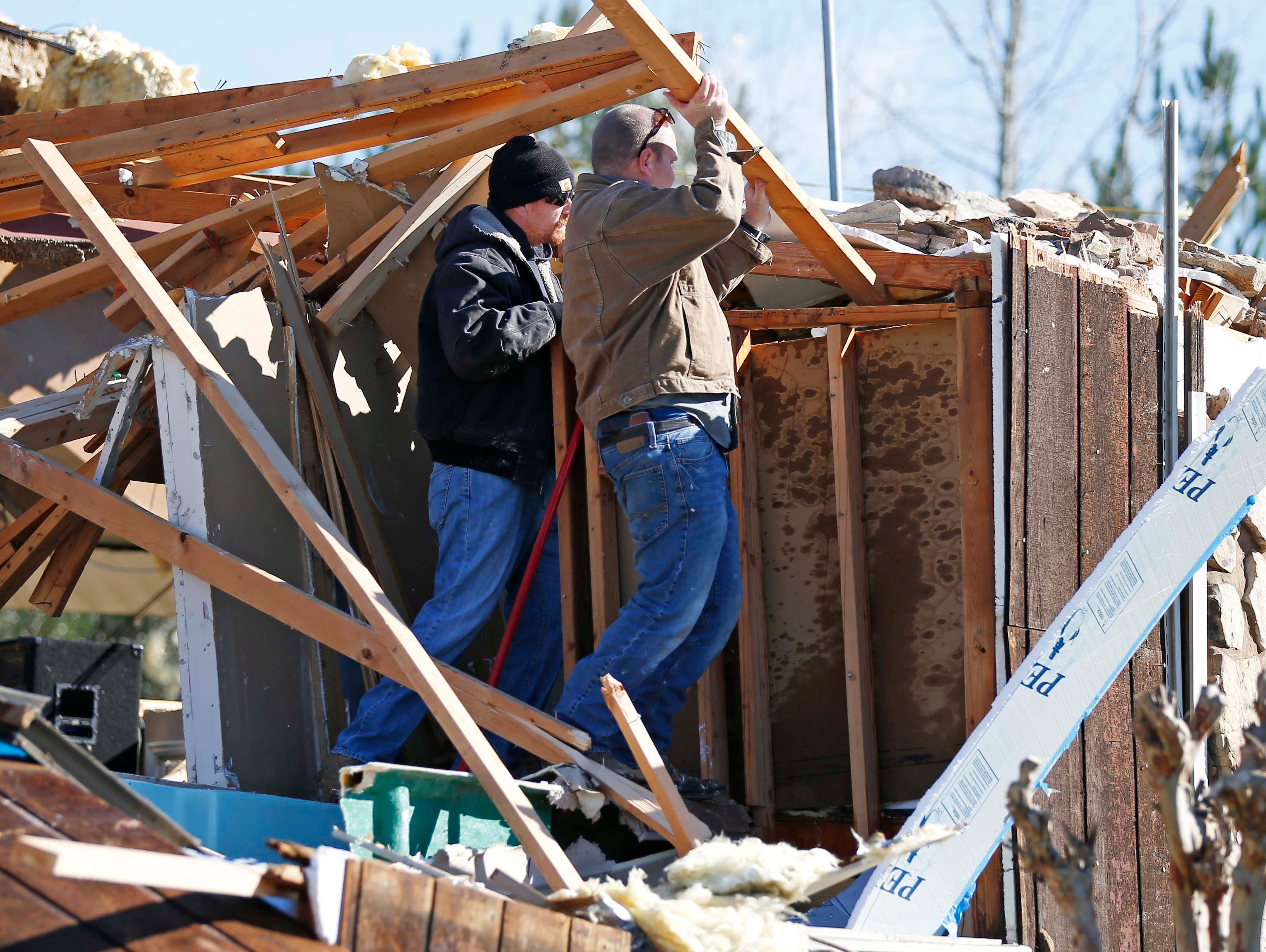 Church members lift beams as they try to determine the status of a Hammond organ that was trapped by tornado debris in the First Pentecostal Church in Columbus, Miss., Sunday morning, Feb. 24, 2019. At least one person was killed in town by Saturday's storm that shattered businesses and wrecked homes. (AP Photo/Rogelio V. Solis)