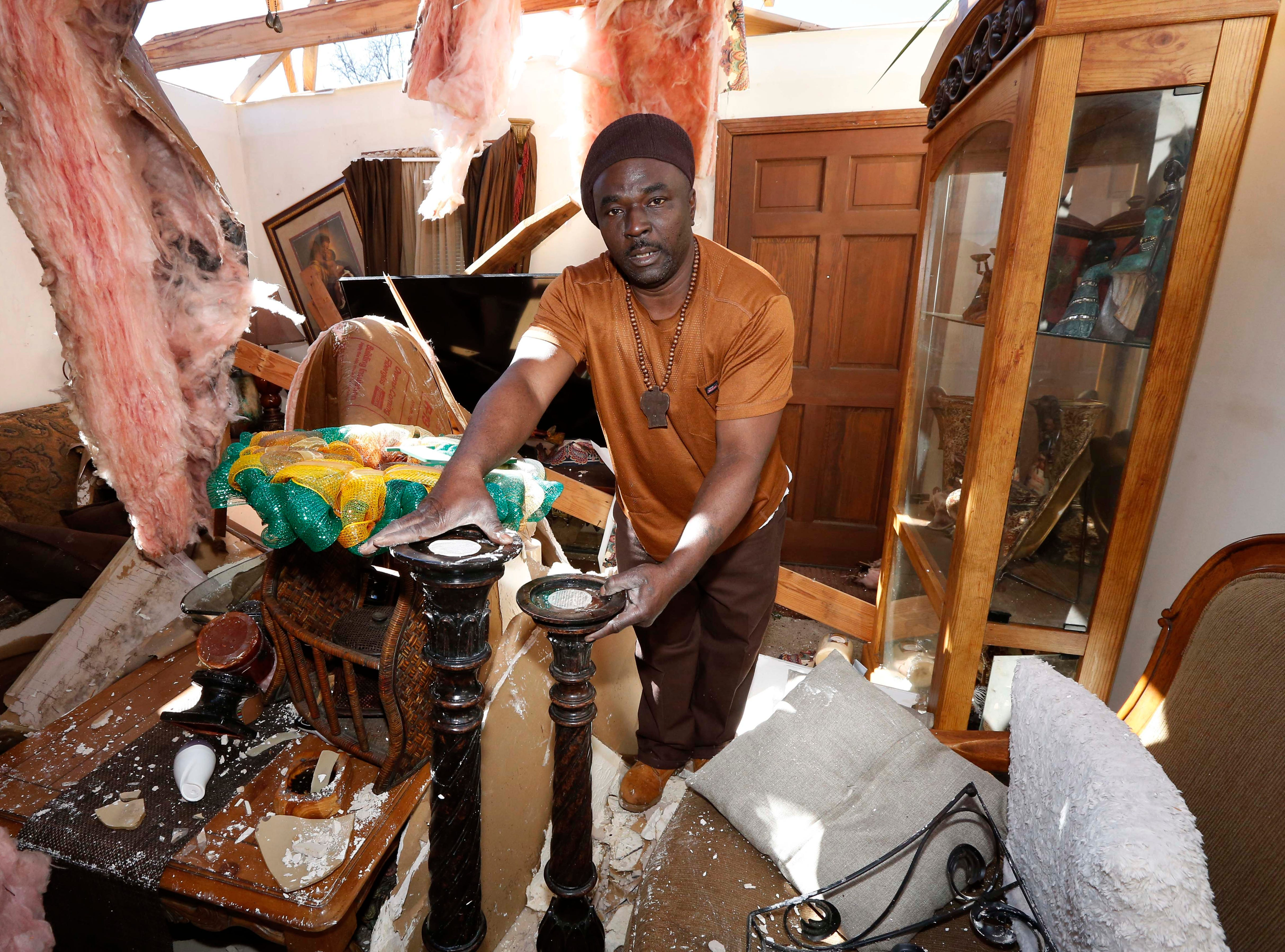 Charles Lowery of Columbus, Miss., rescues carved stands from the remains of his home, Sunday, Feb. 24, 2019, following Saturday's tornado. Lowery lamented not staying at home and protecting his property as his home was looted that evening. (AP Photo/Rogelio V. Solis)